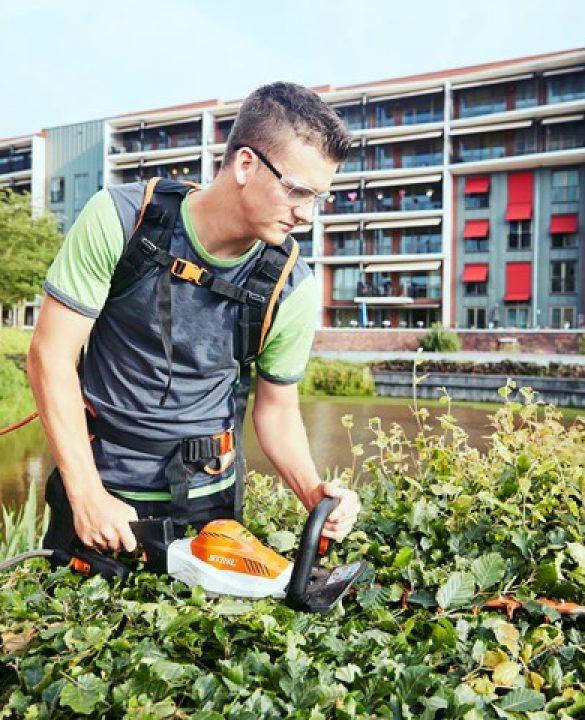 Een medewerker van Donker Groen verzorgt het groen in Delfshaven met elektrisch gereedschap.