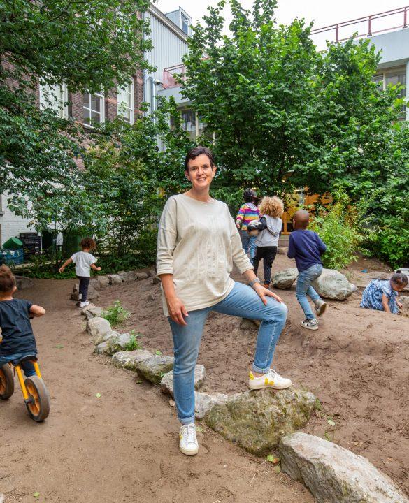Schooldirecteur Annemarie van Oers en leerlingen op het nieuwe groenblauwe schoolplein.
