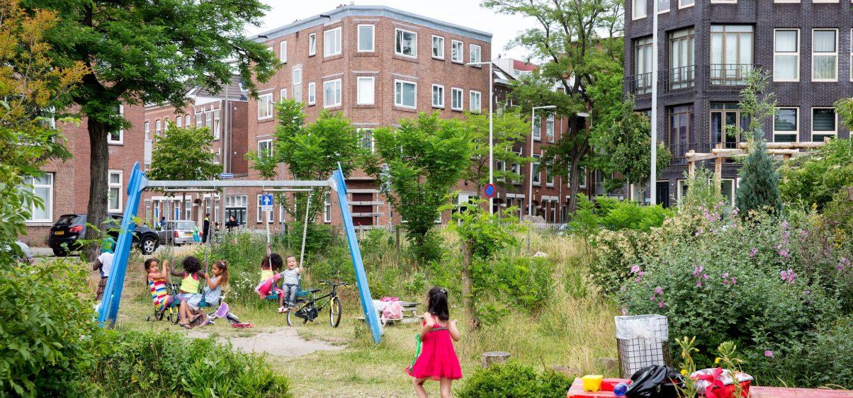 Kinderen spelen in een speeltuin met veel groen